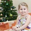 Royalty-Free Stock Photo: Small smiling girl sitting on couch behind christmas tree