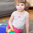 Portrait of small girl playing with bricks on floor — Stock Photo