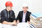 Architect and construction engineer discussing plan in office room — Stock Photo