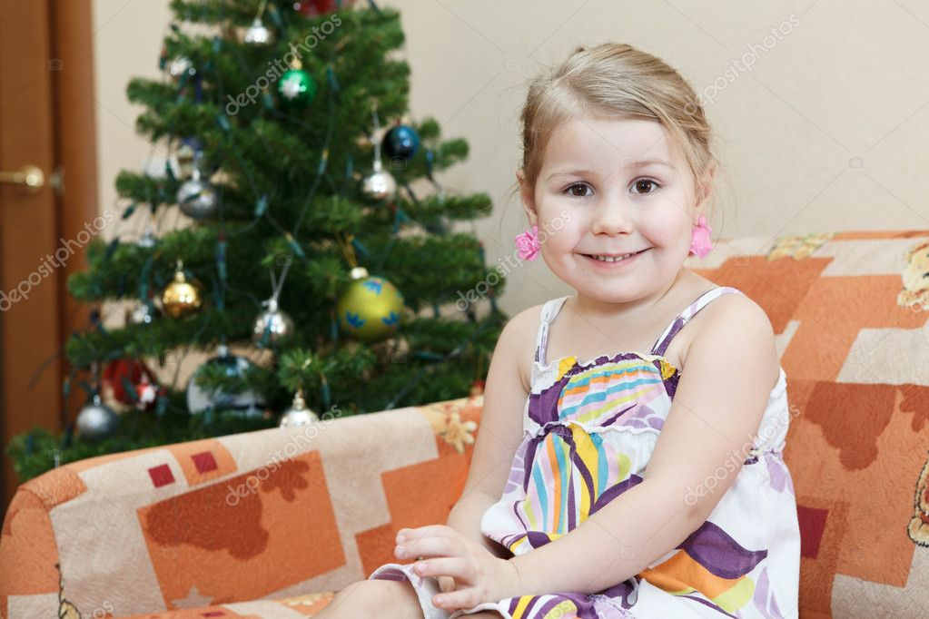 Small smiling girl sitting on couch behind christmas tree — Zdjęcie stockowe #8878507