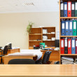 Modern office interior with tables, chairs and bookcases — Stockfoto
