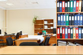 Modern office interior with tables, chairs and bookcases — Stock Photo