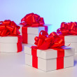 Four white gift boxes with red satin ribbon — Stock Photo