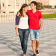 Happy Young Couple Walking Embraced - Stock Photo