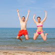 Happy Couple Jumping on the Beach at Seaside — Stock Photo #8425059