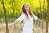 Mujer joven afuera con los brazos abiertos, sensación de libertad — Foto de Stock