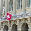 Bundeshaus Facade with Swiss Flag in Bern, Switzerland - Stock Photo