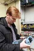 Telecom engineer looking at reflectometer — Stock Photo