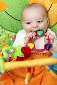 Happy baby bites rattle — Stock Photo