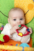 Baby with rattle ring — Stock Photo