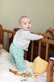 Baby standing in cot — Stock Photo