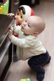 Kid mounting on cupboard — Stock Photo