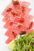 Fish Carpaccio with olives ana salad — Stock Photo
