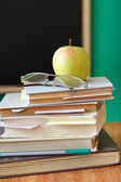 School chalkboard and books — Stock Photo