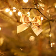 Gold bow on the christmas tree - Stock Photo