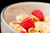 Cornflakes with milk and raspberries — Stock Photo