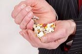 Man holding pills — Stock Photo