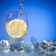 Water, ice and lemon in glass — Stock Photo