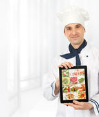 Cook man showing a digital tablet with menu — Stock Photo