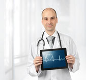 Smiling doctor with hearts beat diagram on a tablet computer — Stock Photo