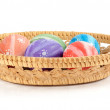 Easter colored eggs in the basket on white background — Stock Photo