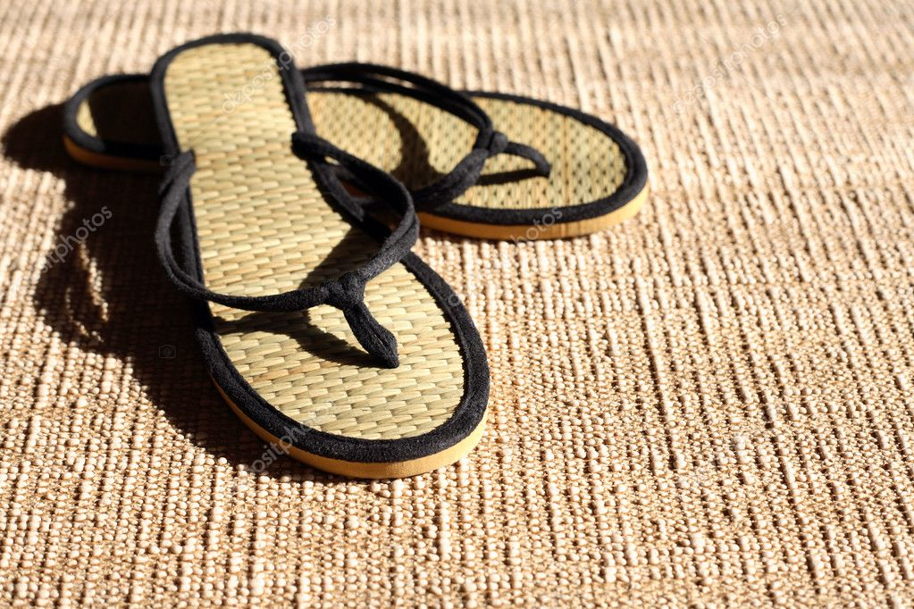 Pair of female summer thongs on jute surface under sunbeam — Stock Photo #10711066