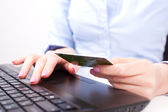 Business woman with credit card, typing — Stock Photo