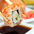 Sushi roll in chopsticks — Stock Photo