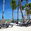 Chaise longues on tropical beach — Stock Photo