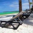 Chaise-longues on tropical beach - Stock Photo
