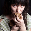 Beggar woman eating bread — Stockfoto