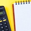 Stock Photo: Notepad and calculator on yellow background.