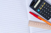 Pen, calculator and a ruler on notebook. — Stock Photo