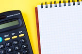 Notepad and calculator on yellow background. — Stock Photo