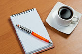 Notebook with pen and coffee on table. — Stock Photo