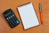 Calculator, notepad and pen on wooden background. — Stock Photo