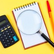 Electronic calculator, notepad and magnifying glass on yellow. — Stock fotografie