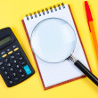 Electronic calculator, notepad and magnifying glass on yellow. — Photo