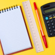 Calculator and notepad on yellow background top view. — Stock Photo #8125459