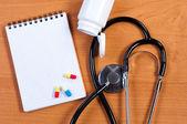 Stethoscoop, kladblok en pillen op tafel. bekijken van bovenaf. — Stockfoto