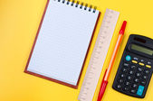 Pocketbook and calculator on yellow background. — Foto Stock