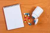 Notebpad and pills on table top view. — Stock Photo