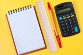 Calculator and notepad on yellow background top view. — Stock Photo