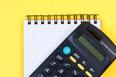 Calculator and notepad close-up view above. — Stock Photo