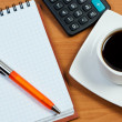 Coffee, notepad with pen and calculator on work-table. - Stock Photo