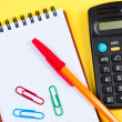 Notepad with pen and paper clips, calculator near. - Stock Photo