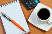 Coffee, notepad with pen and calculator on work-table. — Stock Photo
