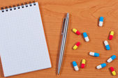Notebook, pen and pills on table top view. — Stock Photo