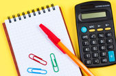 Notepad with pen and paper clips, calculator near. — Stock Photo