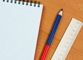 Pad, wooden ruler and pencil on table. — Stock Photo